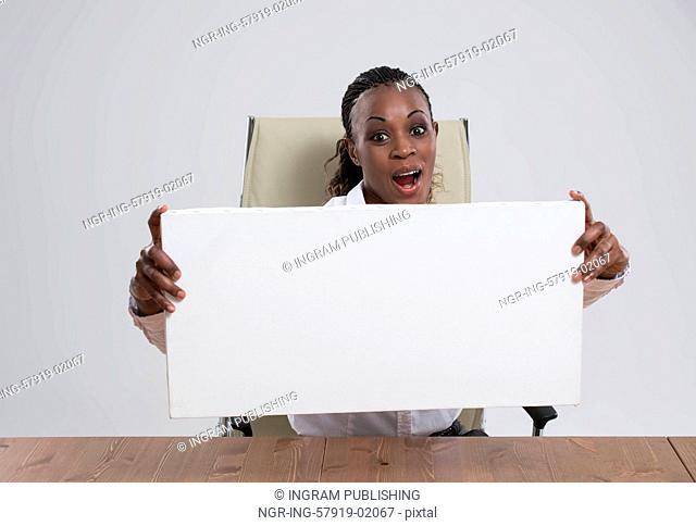 Smiling African Business woman portrait sitting at workplace with blank white board on gray isolated background Female model with long hair