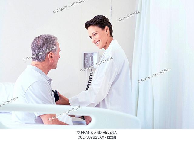 Female doctor using blood pressure gauge on senior male patient on hospital bed