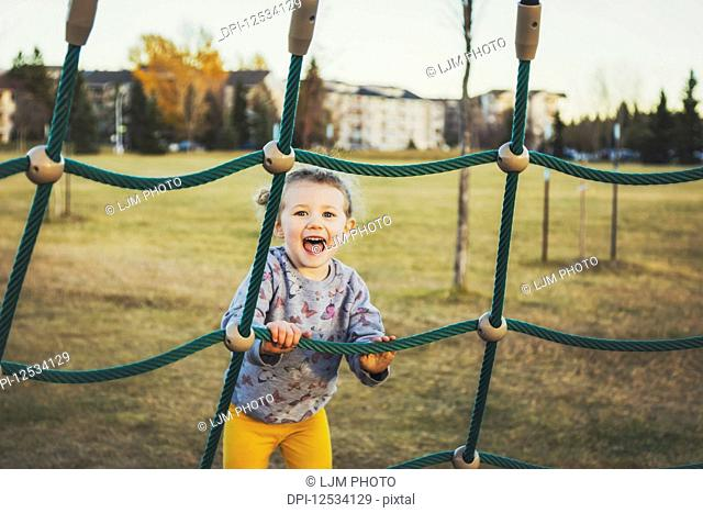 A young girl climbing on a piece of playground equipment on a warm autumn evening at sunset; Edmonton, Alberta, Canada