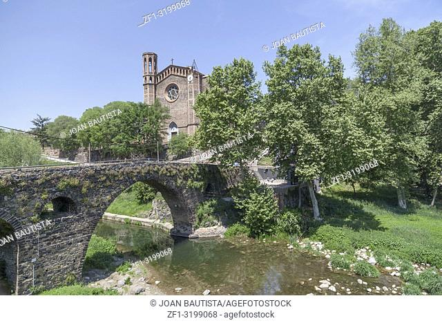 Village view, medieval bridge over river and tower church, Sant Joan les Fonts, Garrotxa, province Girona, Catalonia