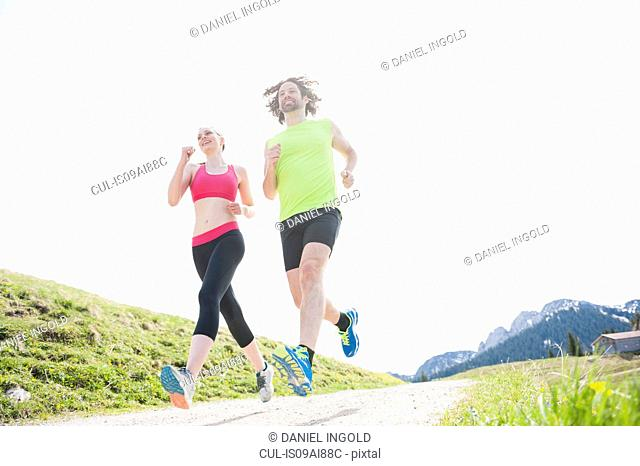 Couple jogging on hilltop, Wallberg, Tegernsee, Bavaria, Germany