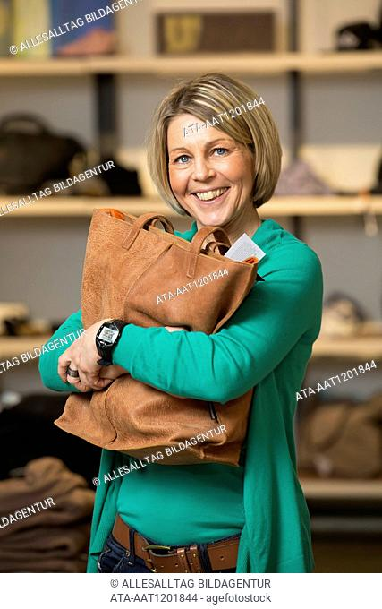 Happy woman with a leather handbag in a boutique