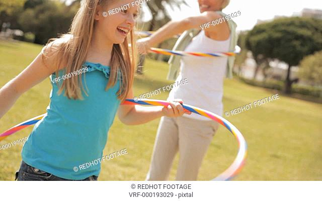 Grandmother and granddaughter playing with hula hoops in park