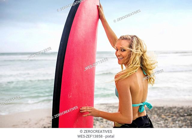 Smiling woman on beach with surfboard