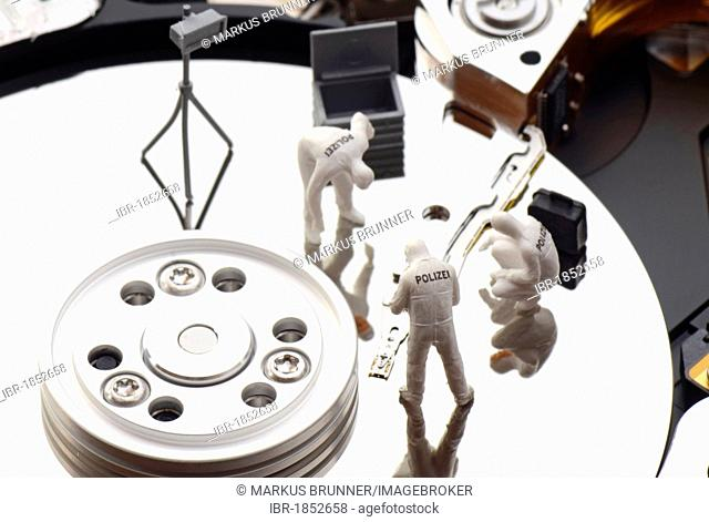 Miniature figures of a police forensic team on a hard drive, symbolic image for data theft or piracy