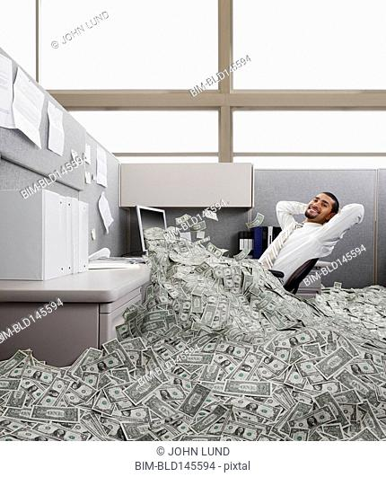 Hispanic businessman in cubicle covered in one dollar bills