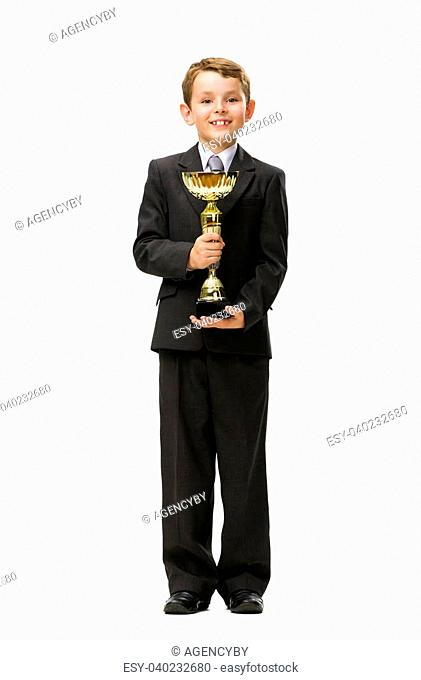 Full-length portrait of little businessman keeping golden cup, isolated on white. Concept of leadership and success