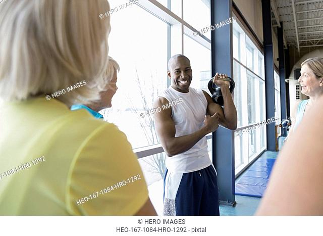 Personal trainer with kettlebell guiding women at gym