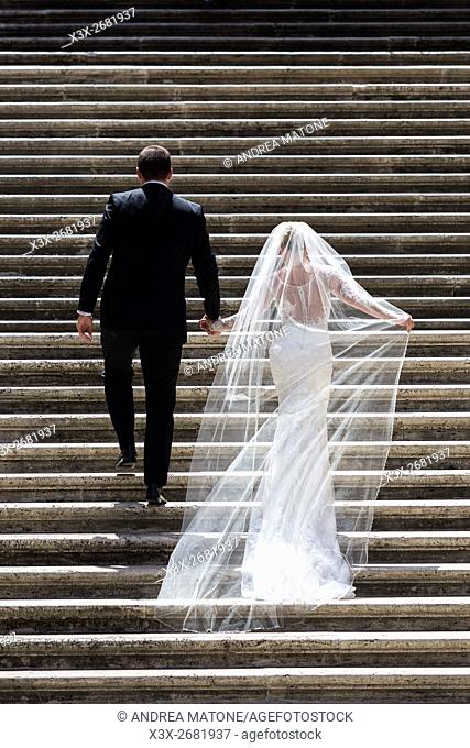 Bride and groom walking up stair