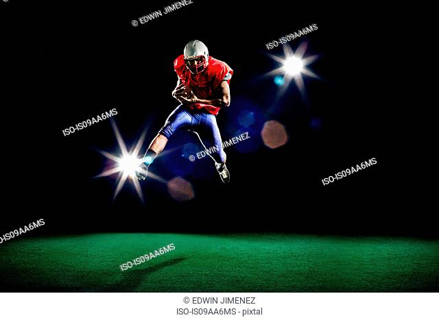 American football player mid air holding ball