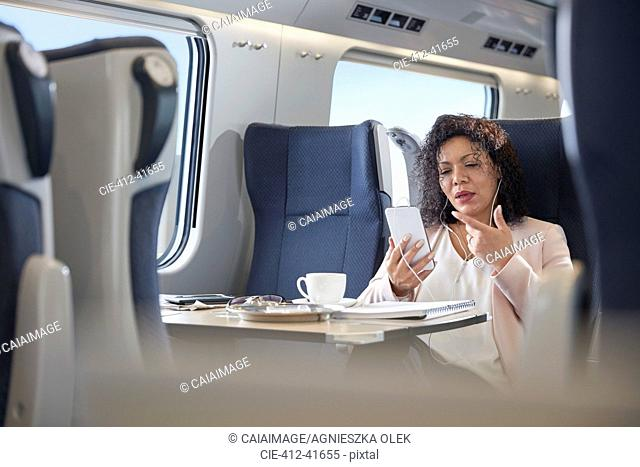 Businesswoman video chatting with headphones and smart phone on passenger train