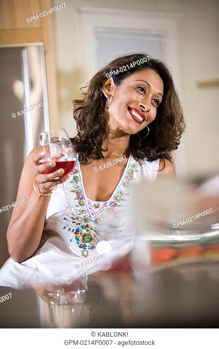 Mid adult Indian woman holding red wine in kitchen