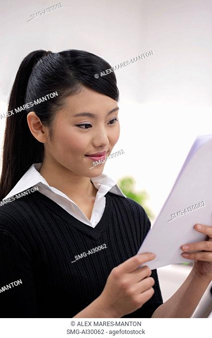 Head shot of young woman looking at paper