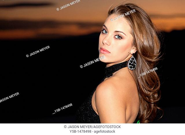 Pretty woman in black dress looking over shoulder during sunset