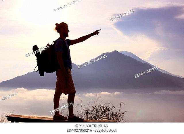 Hiker walking along a mountain path. Sunrise on top of mountain