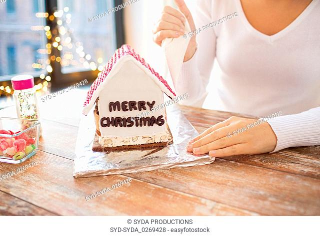 woman making gingerbread house on christmas