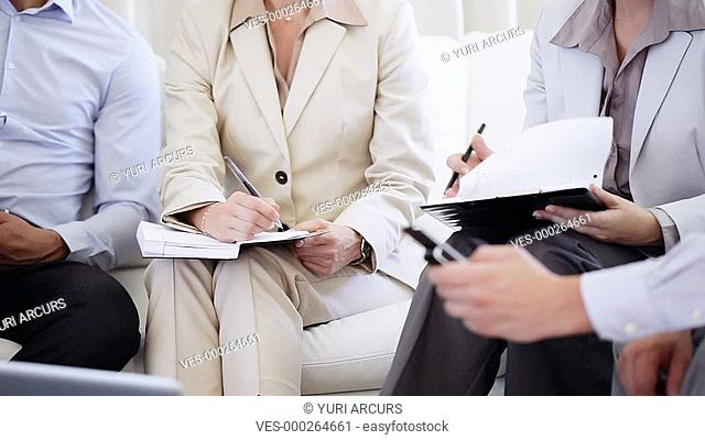 Closeup footage of a group of businesspeople sitting on a couch and making notes
