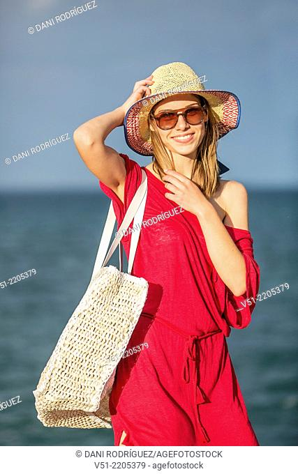 Pretty young woman happy arriving at the beach