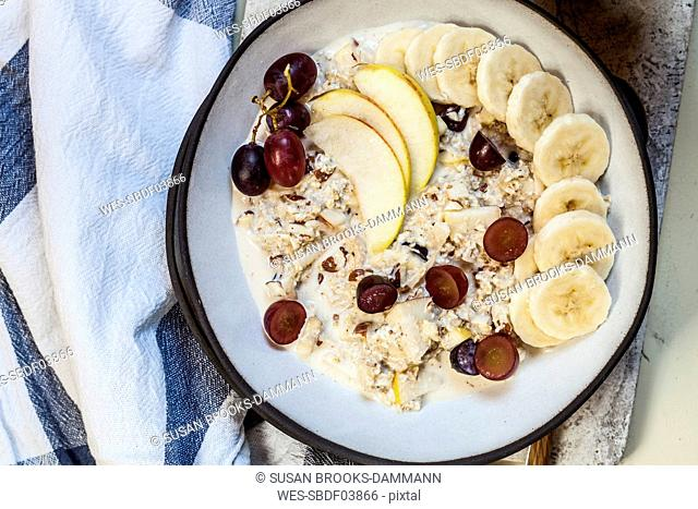 Muesli bowl with bananas, apples, grapes, with coffee