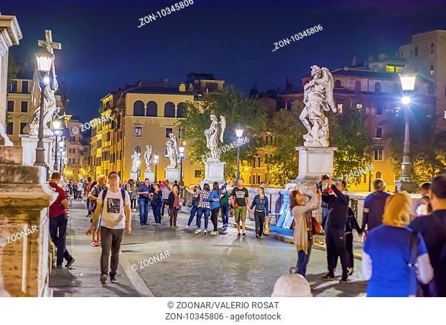 Tourists walking on Saint Angel Bridge in Rome