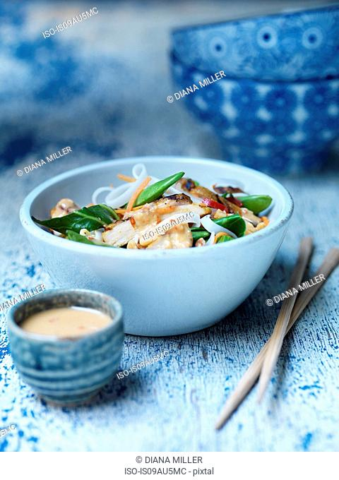 Bowl of spicy peanut chicken, satay sauce, fresh vegetables and noodles with chopsticks on blue surface