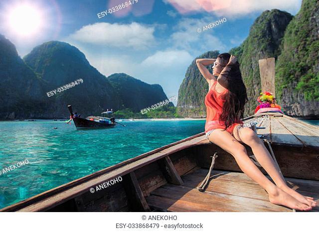 Asian lady relax on long tail boat at maya beach, Phi Phi island near Phuket in Thailand