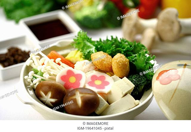 Pot of raw vegetables, mushroom and tofu, food in the background