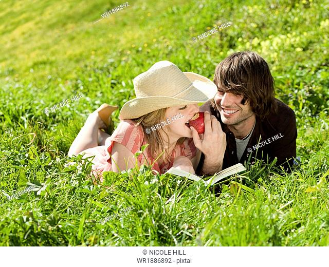 Couple eating apple and lying on grass