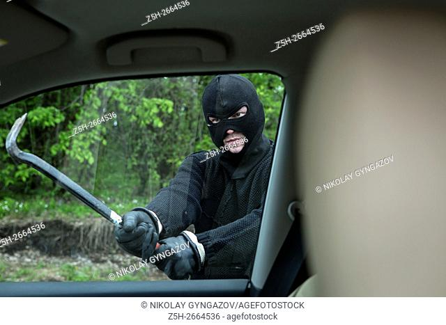 Russia. Theft Auto in a black mask breaks the glass of the machine