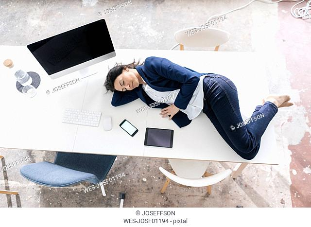 Businesswoman sleeping on desk in the office