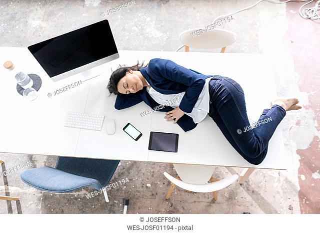 Businesswoman sleeping on desk in the office