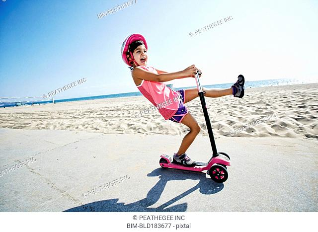Girl riding scooter at beach