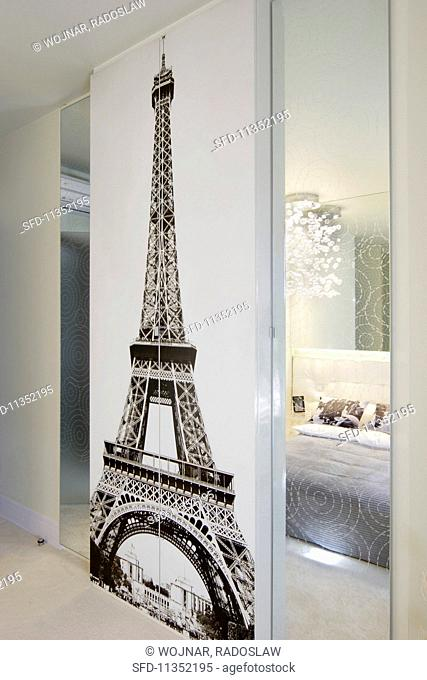 A black-and-white wall picture of the Eiffel Tower, flanked by mirrors reflecting an elegant bedroom