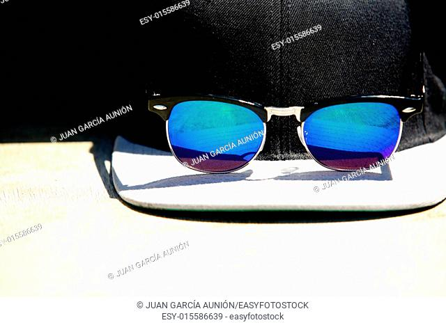 Black cap and blue sunglasses with a reflections. Summer protector for sun