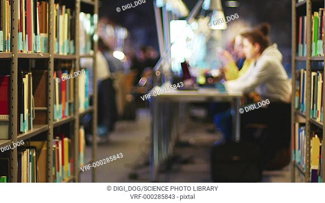 Students studying in library, with books on bookshelves