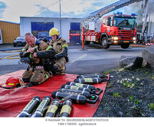 Firefighter assisting team member with oxygen tanks  Auto repair shop on fire in suburb of Reykjavik, Iceland