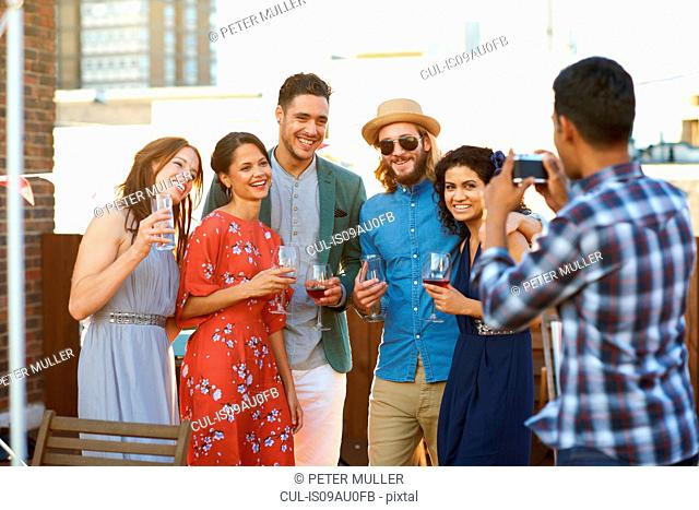 Friends taking photograph at early evening party