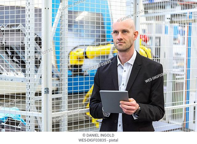 Businessman with tablet in modern factory