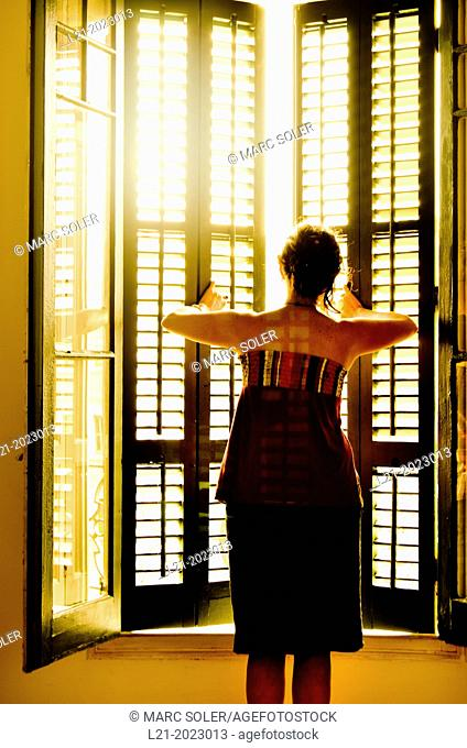 Single woman opening a window