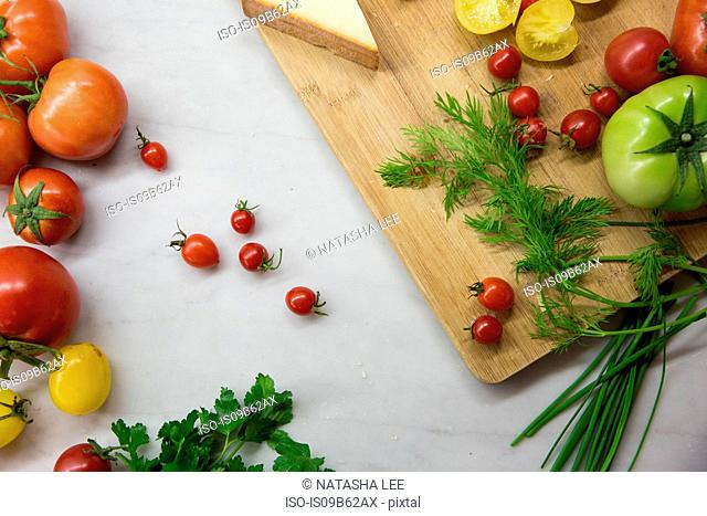 Overhead view of chopping board with heirloom tomatoes, cheese and dill