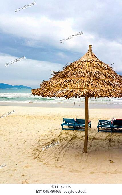 Sun beds and Palm shelter at the China Beach in Da Nang, Vietnam. It is also called Non Nuoc Beach. South China Sea on the background