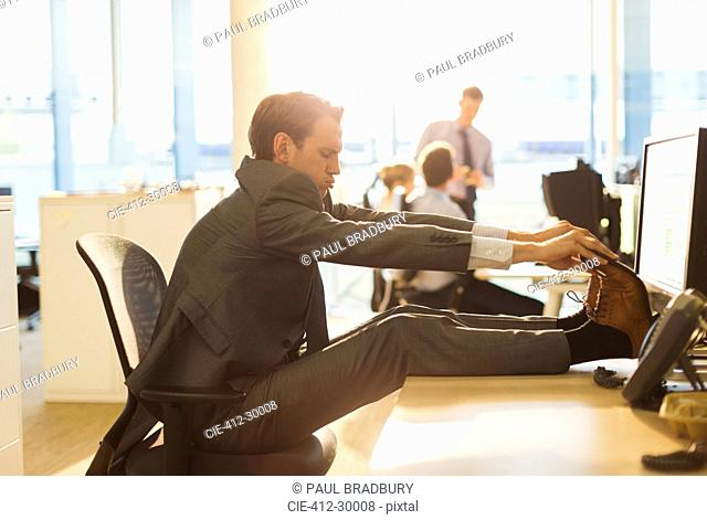 Businessman stretching feet on desk in office