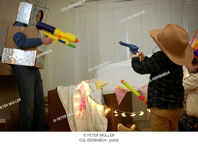 Senior man in robot costume shooting toy guns with dressed up grandchildren