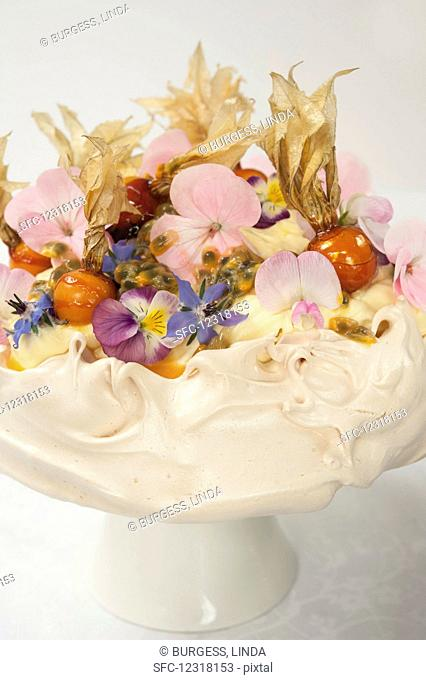 A meringue cake garnished with flowers and caramelised physalis
