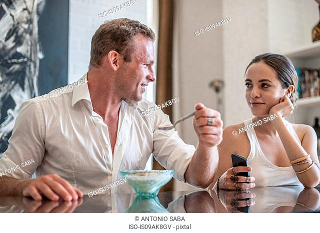 Young couple chatting and eating at kitchen table