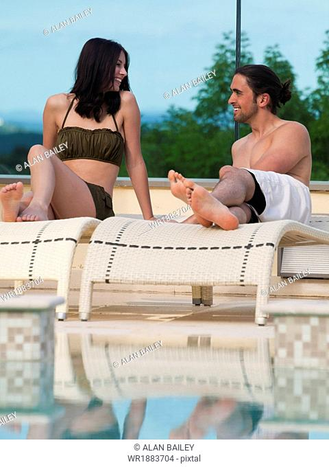 Italy, Young couple relaxing by swimming pool