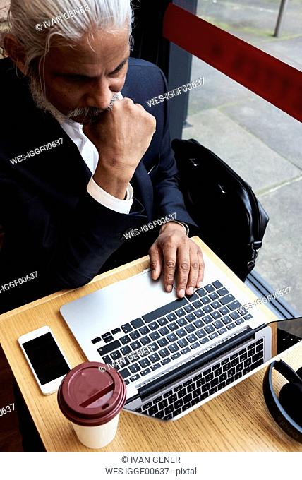 Senior businessman working on laptop in a coffee shop