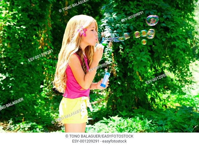 Children blowing soap bubbles in outdoor forest with fashion pink flower