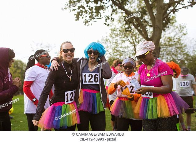 Portrait playful female runners in wigs and tutus at charity run in park