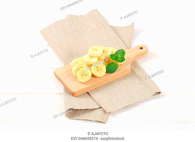 pile of sliced banana on wooden cutting board